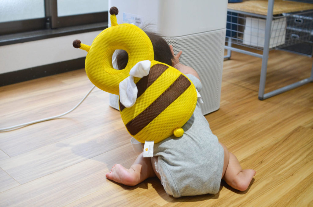 転倒防止リュック、ベビーヘッドガードを背負ってつかまり立ちしようとしている7ヶ月の娘。