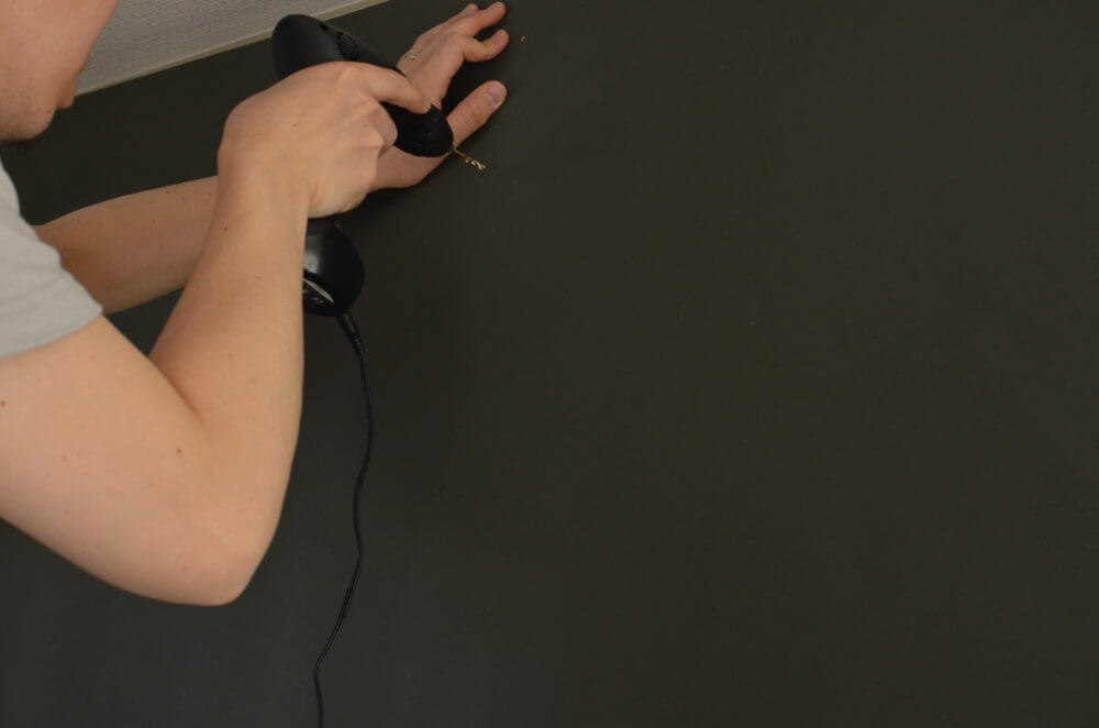 ディアウォールでDIYした柱に、黒板塗料のベニヤを取り付けていく。
