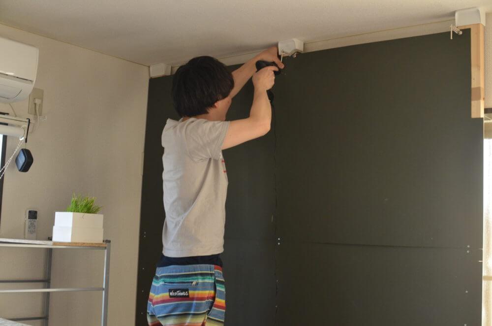 ディアウォールでDIYした柱に黒板塗料のベニヤを取り付ける。