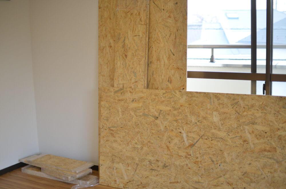 引っ越したての賃貸の壁にDIYの材料が立てかけてあります。