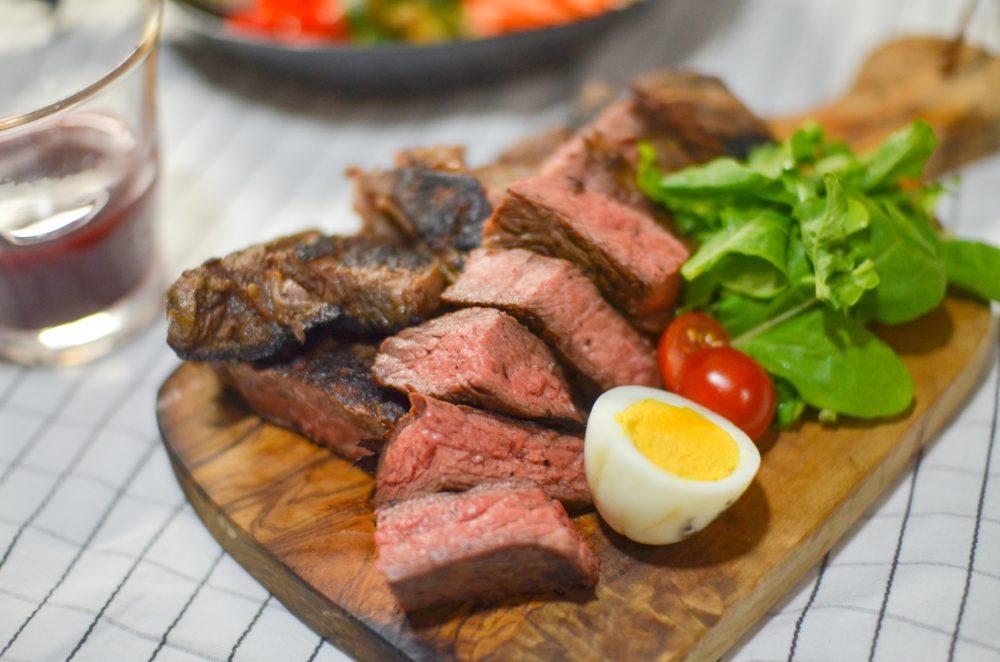 ピンク色に火が通ったステーキをサラダと一緒に盛り付け。