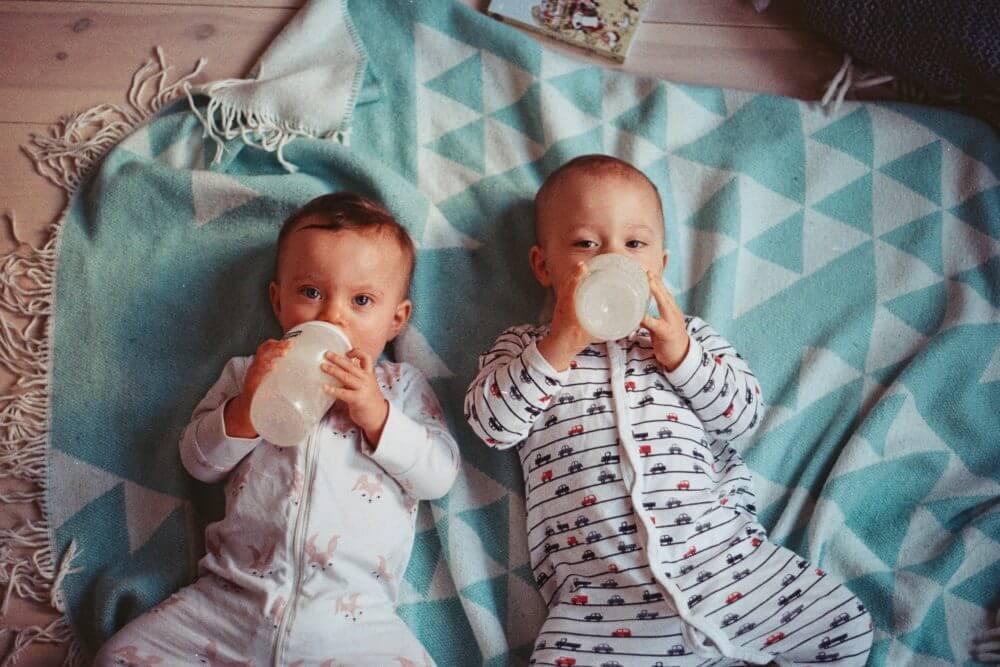 自分でミルクを飲む赤ちゃん二人