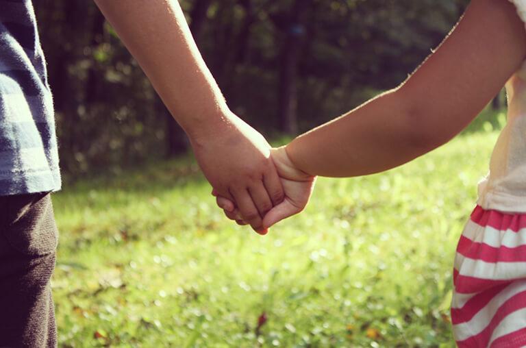 手をつなく男女の子どもの写真