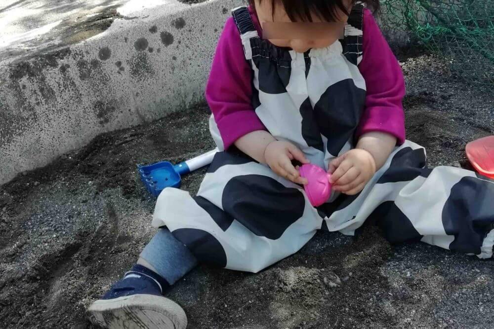 「お砂場着」を着て砂遊びする娘