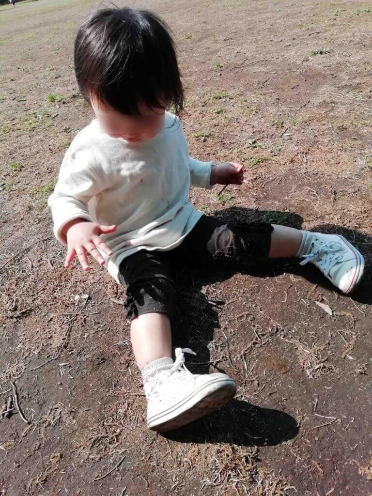 洋服を砂だらけにして遊ぶ娘